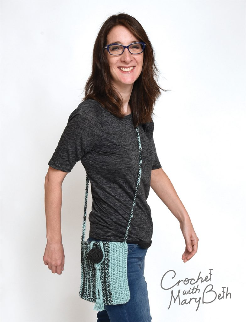 A woman modeling the Ball Button Crossbody Bag.  A free crochet bag pattern that can be found on the website crochet with mary beth.