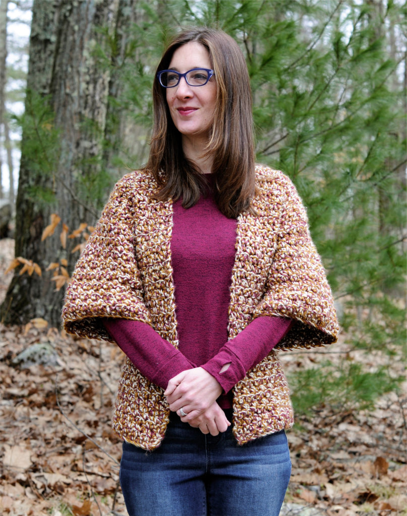 Woman wearing crochet cardigan looking off to the side.