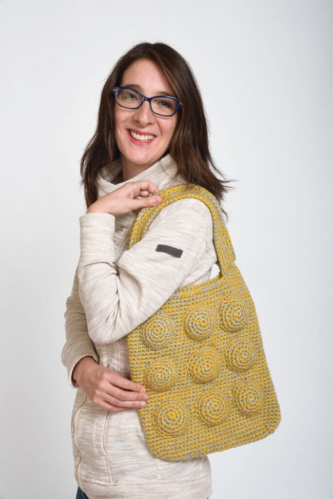 A woman holding the 9 ball tote, a crochet pattern on crochet with Mary Beth.