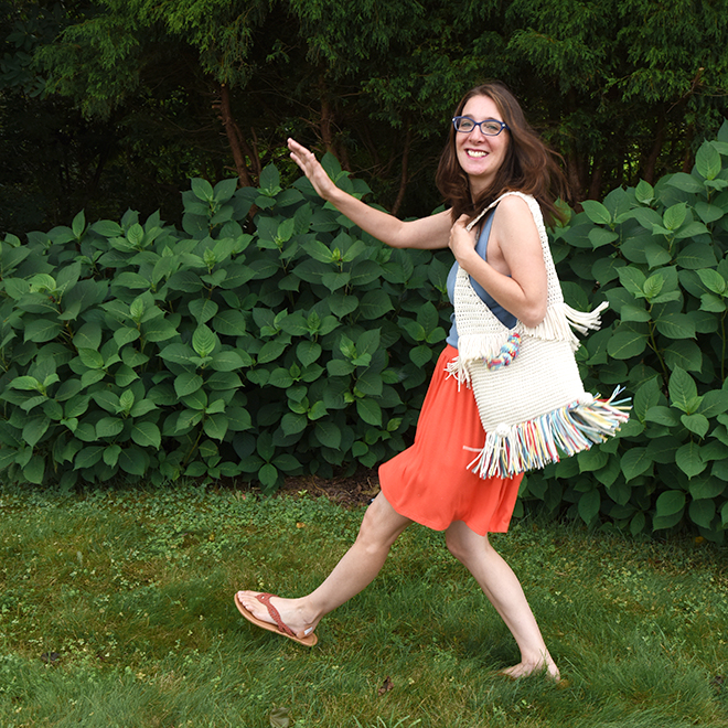 Woman skipping wearing the Super Sunny Tote made from the crochet pattern.