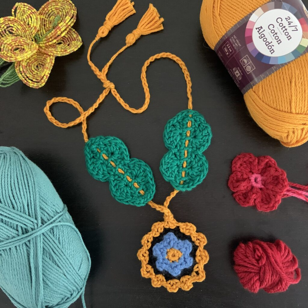 Close up of the Once and Floral Necklace.  This necklace is made with four colors of worsted weight stash yarn.  This crochet project will get your creative juices flowing.