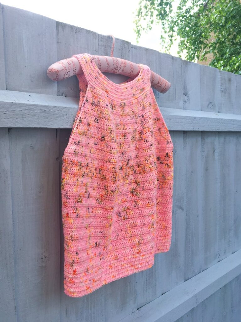 A crochet halter top hanging on a fence.  The ladies crochet top pattern is designed by Dora Does.