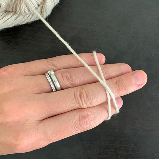 A hand with yarn crossed over the back forming an X shape.